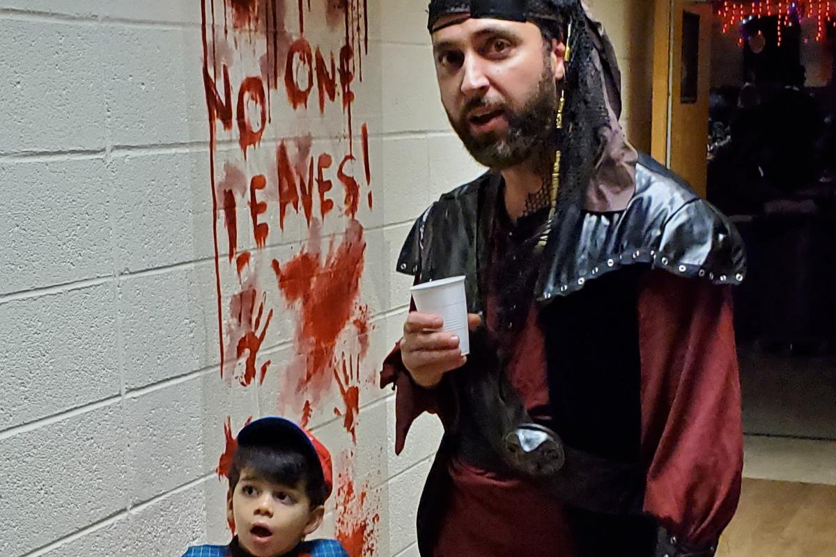 Boy dressed in racecar driver costume and man dressed as pirate in hallway