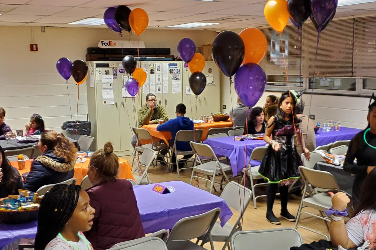 Purple orange and black balloons at tables with purple and orange tablecloths with children and adults doing crafts