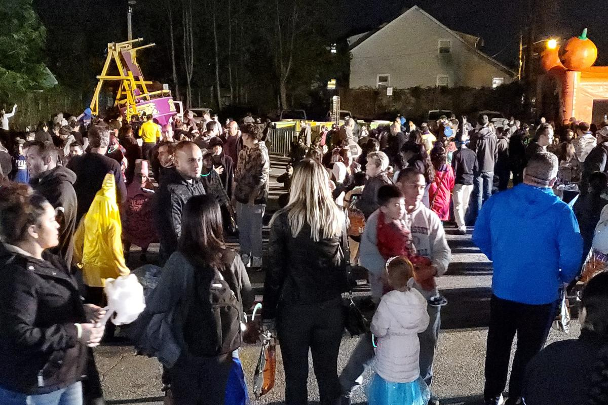 Crowd of parents and children in parking lot with ride on left and bounce house or right and house in distance