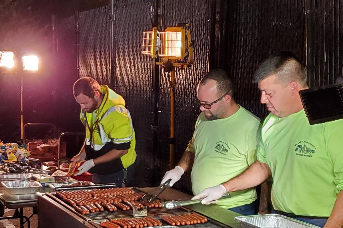 Three men in bright yellow shirts, two cooking a lot of hot dogs at grill