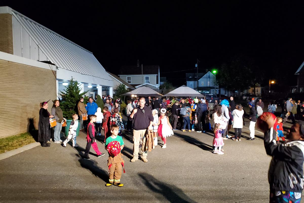 Crowd of parents and children in parking lot with building on left and two canopies in distance