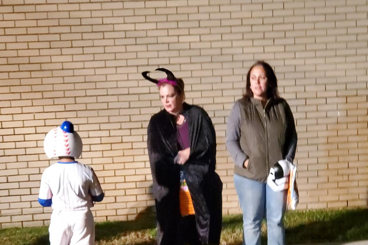 Child in baseball costume and two women