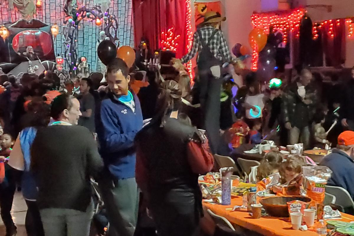Crowd of people indoors room decorated with orange lights and creepy tree and stagecoach