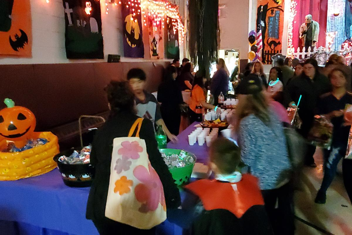 Orange lights and Halloween decorations on wall on left, people and snacks on table on right