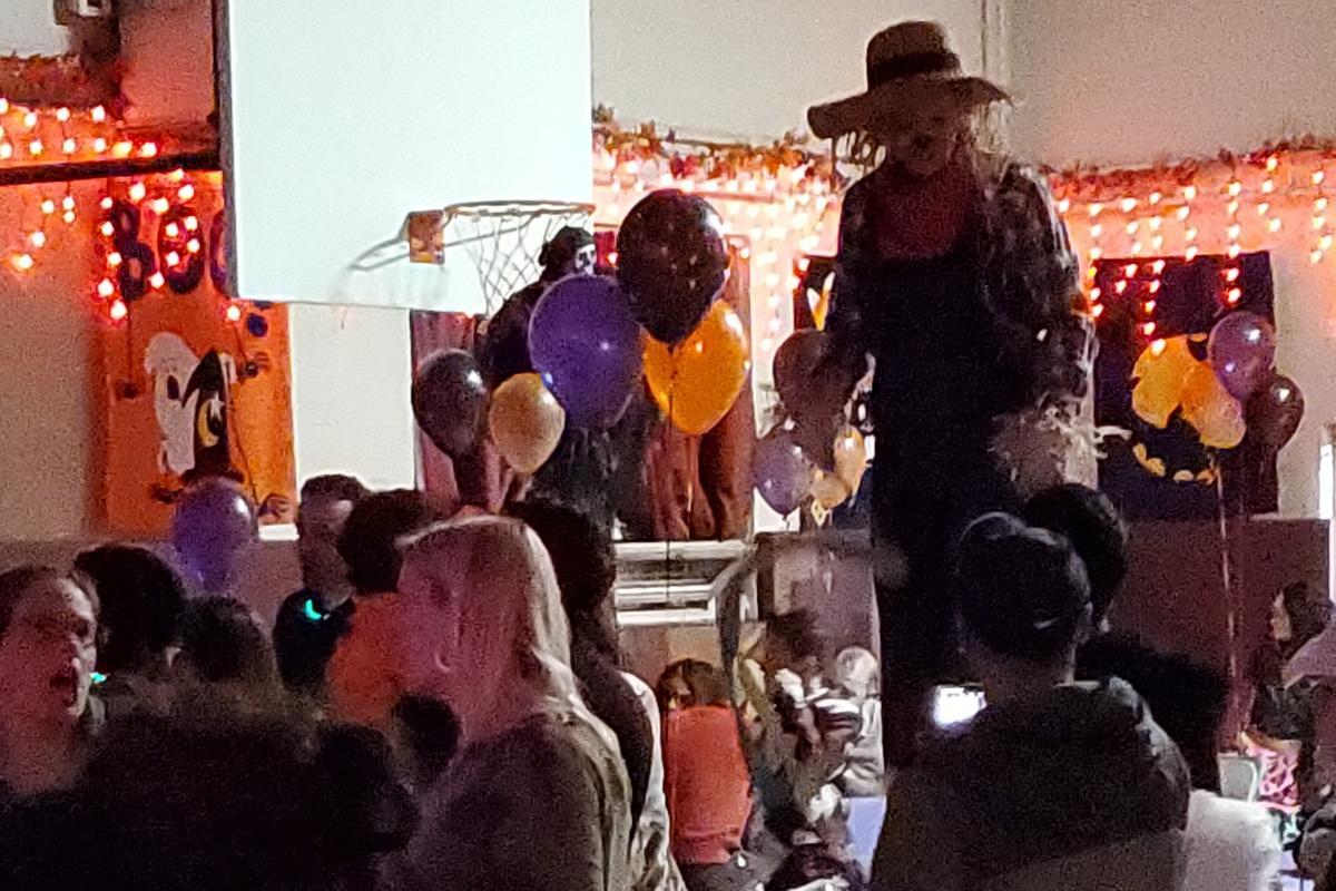 Scarecrow on stilts walking between crowd, orange black purple balloons in back