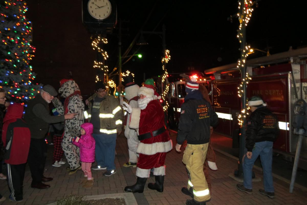 Santa getting off firetruck to arrive at tree lighting ceremony