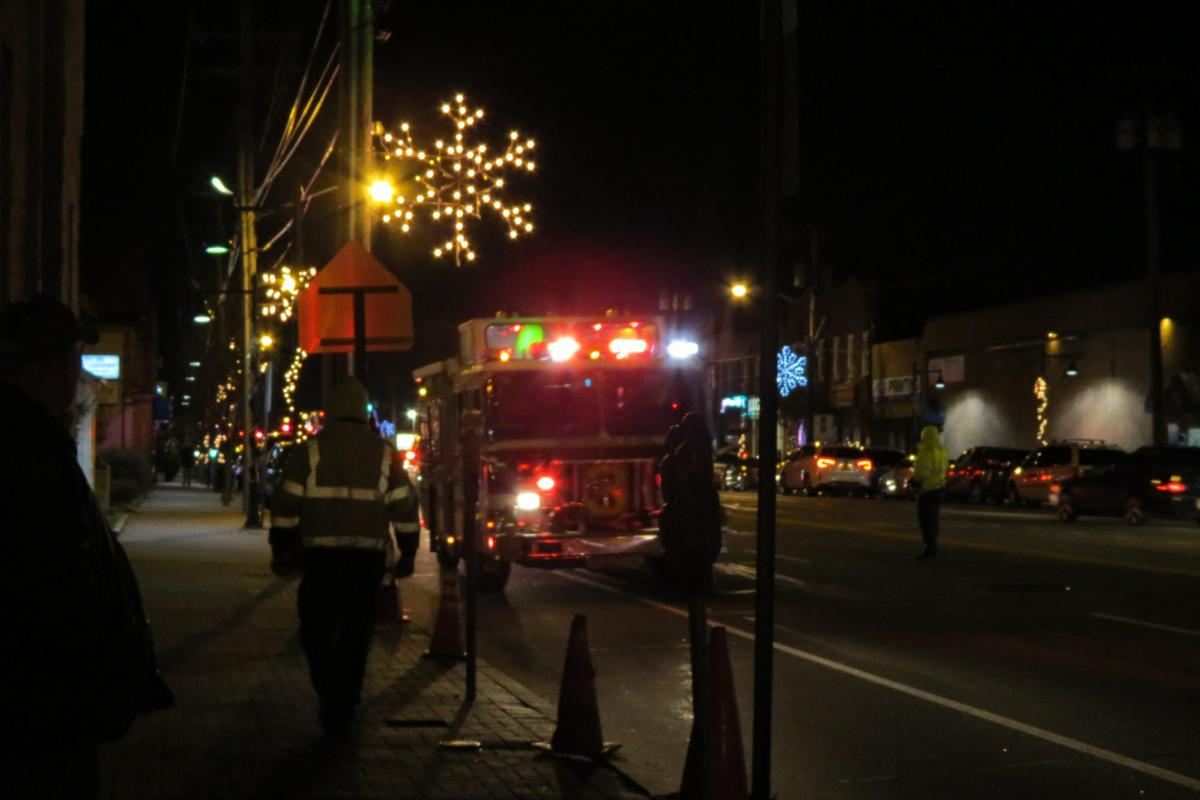 Firetruck with Santa in back coming down dark busy street