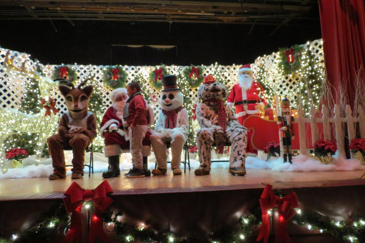 Santa, snowman and reindeer posing with children on stage decorated with Christmas decorations