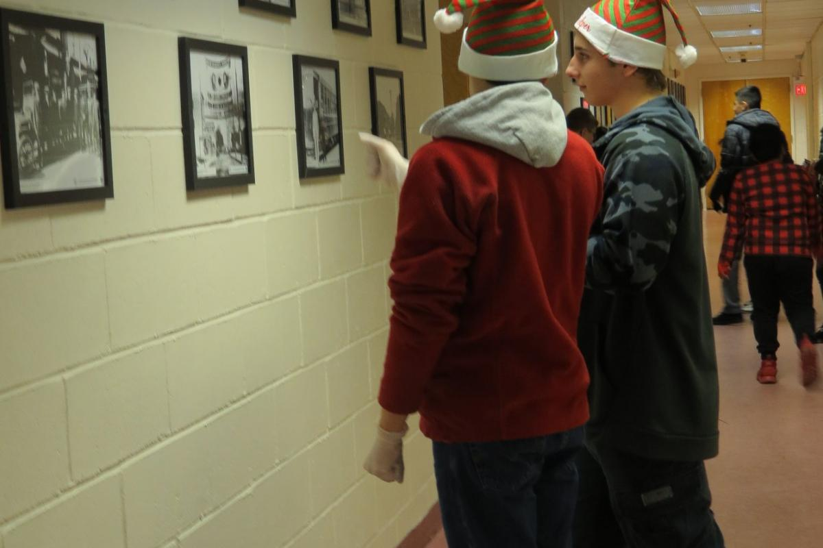 Two junior fireman wearing red santa hats in hallway looking at photos on wall