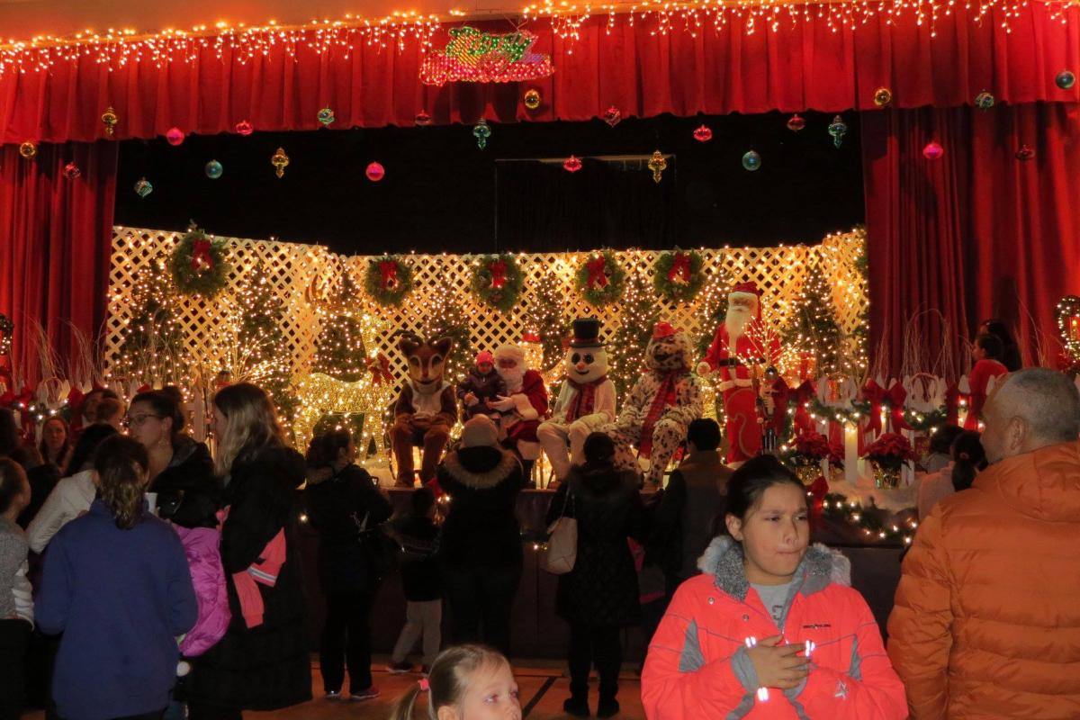 Community center filled with many people and stage decorated with bright lights