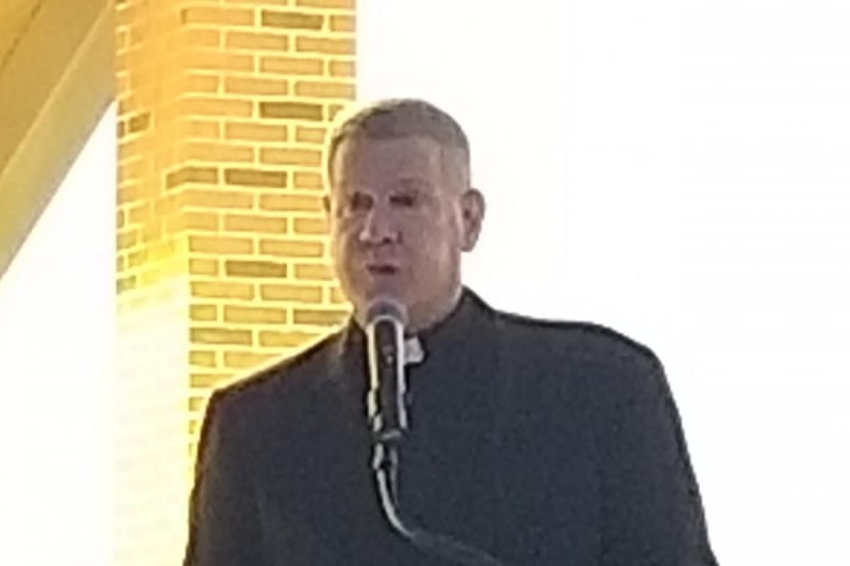 Priest at podium, orange Village of Mineola logo on podium